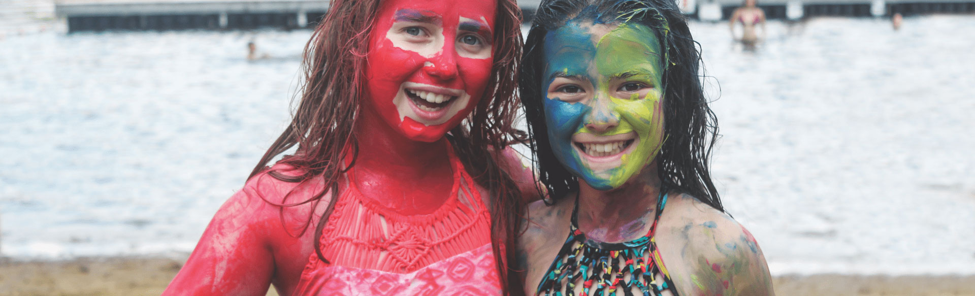 Two girls smiling with paint over their face