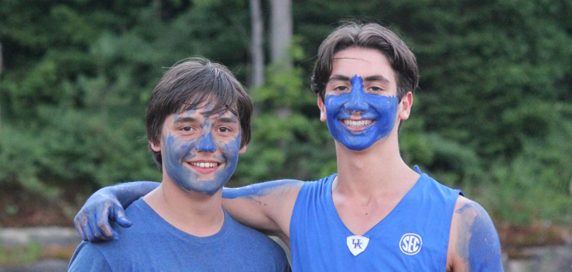 Two boys posing for a photo with paint on their face