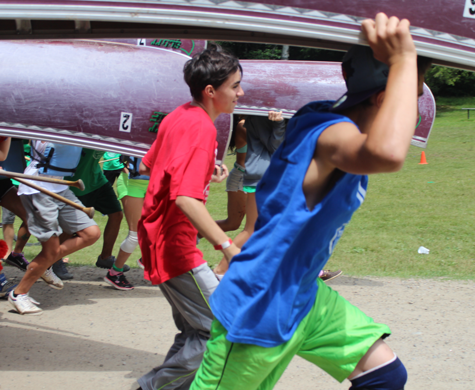Group of boys holding a canoe over their head and walking