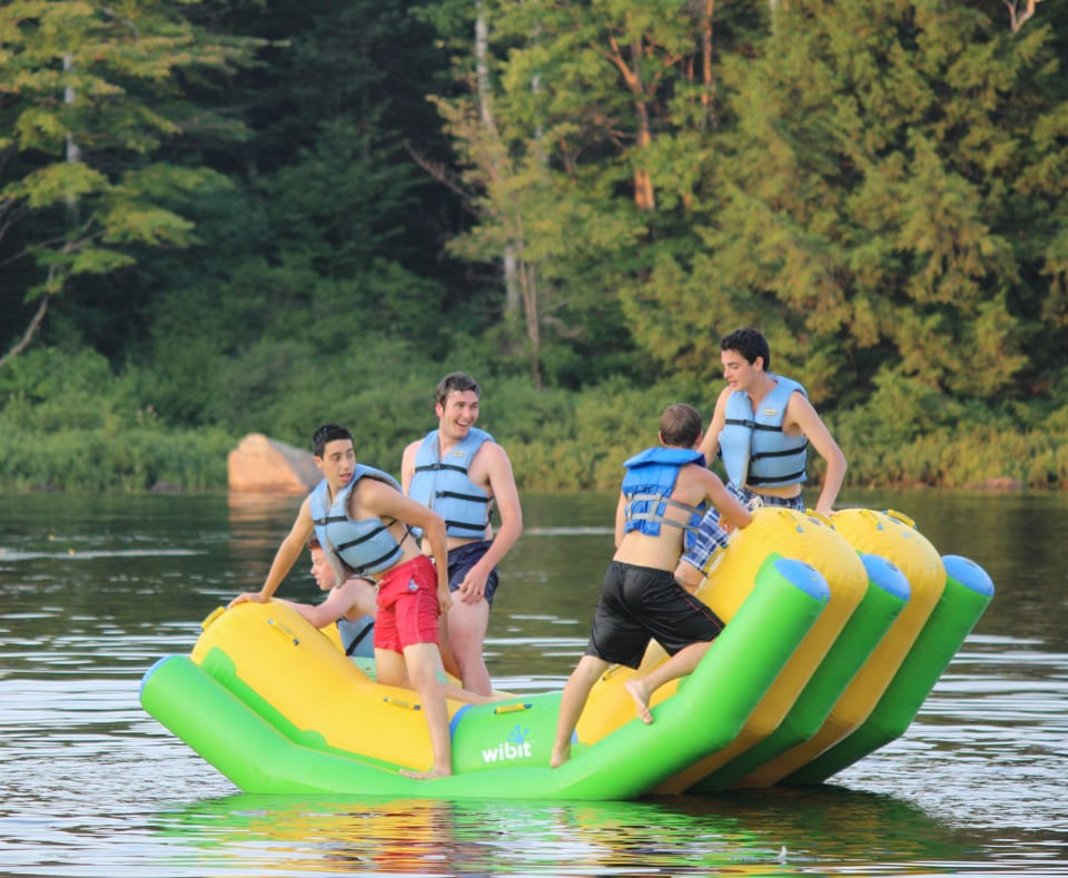 Campers on a flotation device on the lake