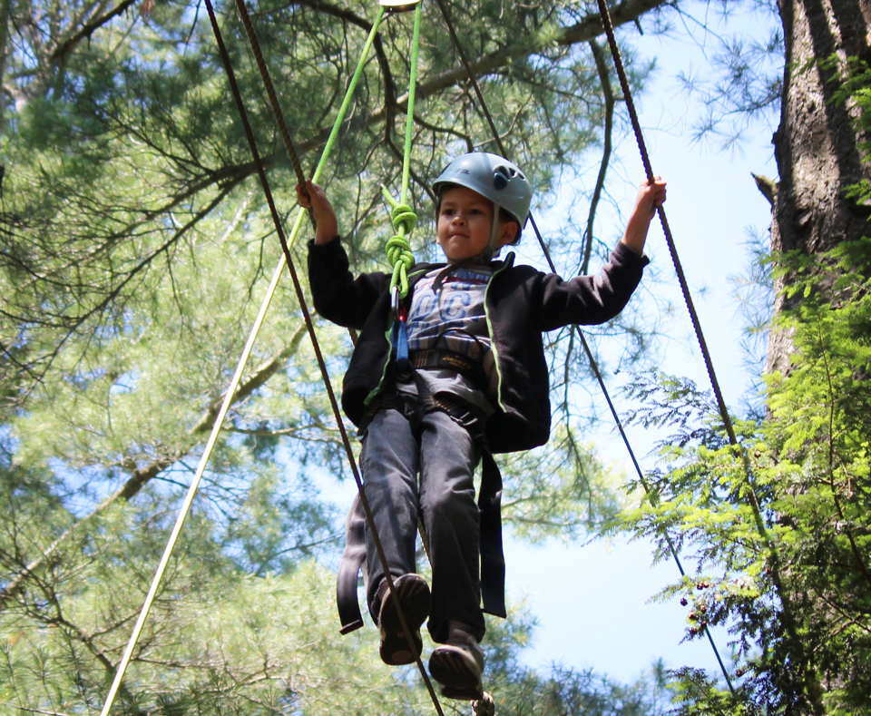 Boy walking on a rope tied to trees