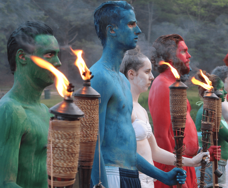 Group of people colored with body paint holding torches