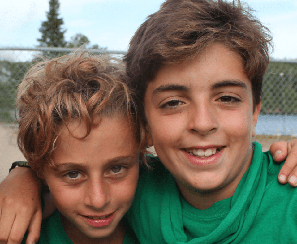 Three boys wrapping arms around each other and posing for a photo
