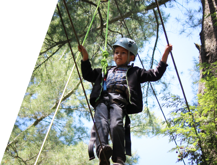 Boy doing ropes course at Camp Tamarack